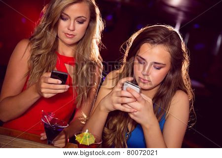 Pretty friends looking at smartphones at the nightclub