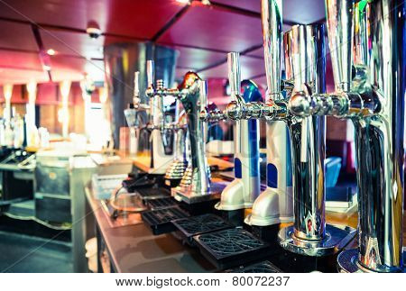 Shiny beer taps in a row in a bar