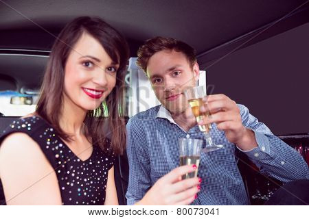 Happy couple drinking champagne in limousine on a night out