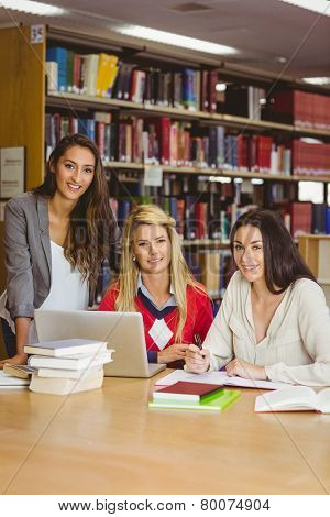 Portrait of three classmates working together in library