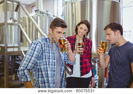 Young hipsters tasting beer together in the factory