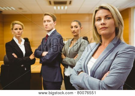 Serious lawyer standing with arms crossed in the court room