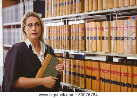 Serious lawyer holding a book in library