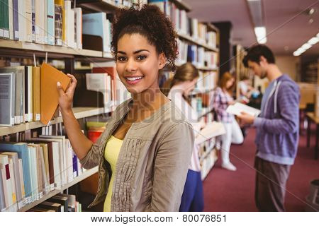 Smiling student picking out a book in library