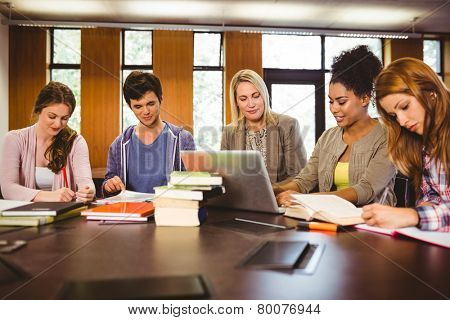 Smiling students working together on an assignment in library