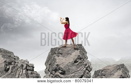 Young woman in red dress on rock playing fife