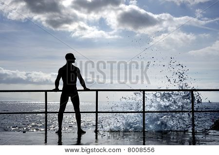 Silhouette of young man standing at the seaside - wave splach