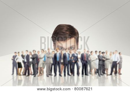Young businessman peeping at people from under table