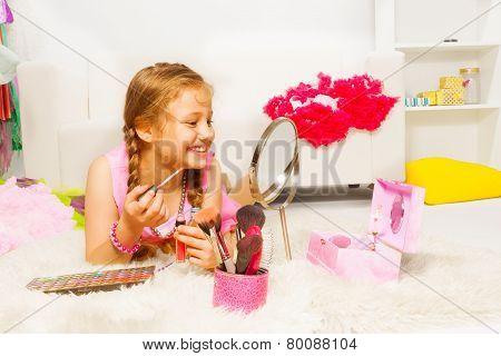 Girl laying on white carpet and applying lip gloss
