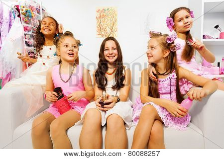 Happy girls with hair-curlers sit on white sofa