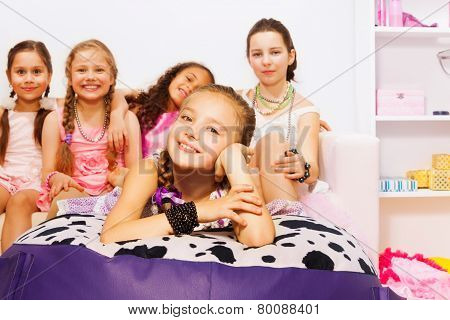 Girls laying and sitting together on big bed