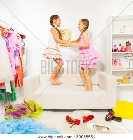 Happy girls jump and hold hands on white sofa