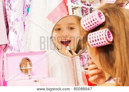 Beautiful girl makes up her face looking in mirror
