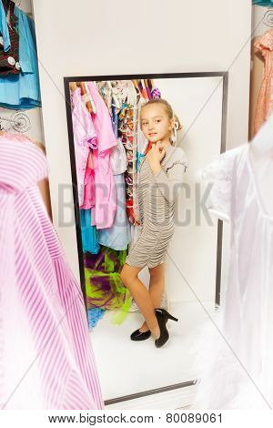 Little girl try on dress in fitting room