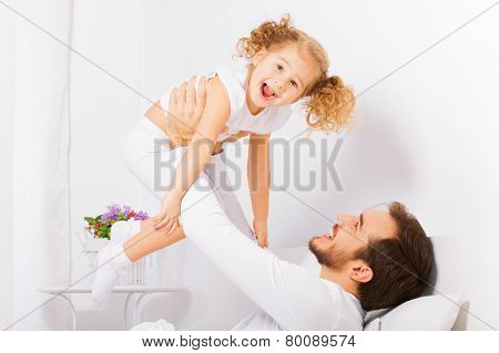 Father holds with arms his laughing daughter