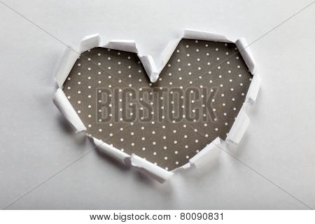 White torn paper heart over grey background