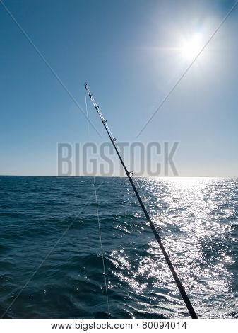 Sun flare and glare across the sea and above a fishing rod.