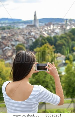 Tourist with smartphone camera in Bern, Switzerland at Rosengarten, the Rose Garden view. Woman taking photograph with smartphone at enjoying view of Berne landmarks and tourist attractions.