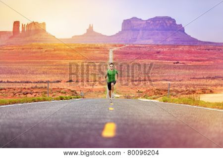 Runner man athlete running sprinting on road by Monument Valley. Concept with sprinter fast training for success. Fit sports fitness model working out in amazing landscape nature. Arizona, Utah, USA.
