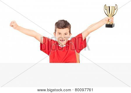 Cheerful junior holding a trophy behind a panel isolated on white background