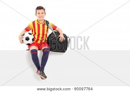 Boy holding a football and sitting on panel isolated on white background
