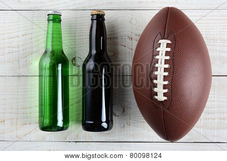 Two beer bottles and an American style football on a rustic whitewashed wood surface. Horizontal format. One green bottle and one brown, both without labels.