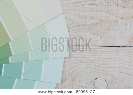 High angle closeup of green paint chip samples fanned out on a rustic white wood table. Horizontal format with copy space.