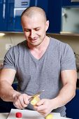 stock photo of ginger man  - handsome man who ginger peels on a table in the kitchen - JPG