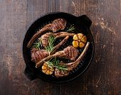 picture of ribs  - Roasted lamb ribs with rosemary and garlic on grill pan on dark background - JPG