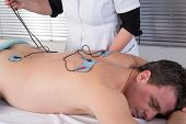 picture of hernia  - A man doing a back massage by electrodes - JPG