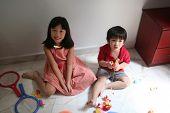 Girl & boy playing toys poster