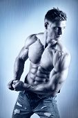 stock photo of abdominal muscle  - Posing young well trained man with perfect abdominal and pectoral muscle on blue metal background - JPG