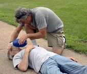 stock photo of cpr  - man giving cpr to a man on a sidewalk - JPG
