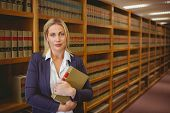 image of librarian  - Female librarian posing and holding a book in library - JPG