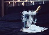 image of champagne glasses  - A bottle of chilled champagne in an ice bucket and two glasses on a bed dark tones - JPG