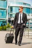 pic of carry-on luggage  - Confident young businessman in full suit carrying suitcase while walking outdoors - JPG