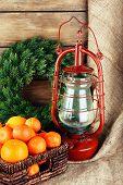 stock photo of kerosene lamp  - Kerosene lamp with wreath and oranges in wicker basket on wooden planks background - JPG