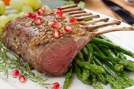 stock photo of pomegranate  - Herb crusted rack of lamb garnished with asparagus green grapes and pomegranates - JPG