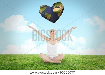 Toned young woman sitting with arms outstretched against field and sky