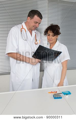 Doctor And Her Assistant Watching His Digital Tablet