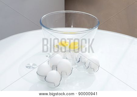 Eggs in the shell near the bowl with a broken egg