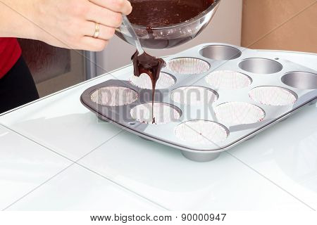 Baker pours chocolate into a mold for baking