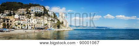 Cetara Italy - October 2 2013: Cetara small beach village on the Amalfi Coast LA beach is defended by an ancient Saracen tower. Bathers on the beach on a warm October day. In the background you can see the city of Salerno