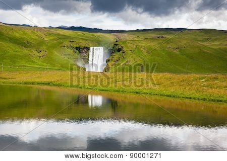 An incredible reflection. Abounding waterfall Skogafoss reflected in a small pond near the road