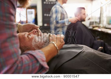 Male Barber Preparing Client For Shave In Shop
