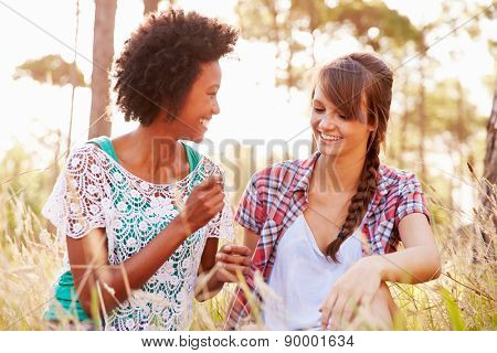 Portrait Of Two Smiling Young Women Sitting In Countryside
