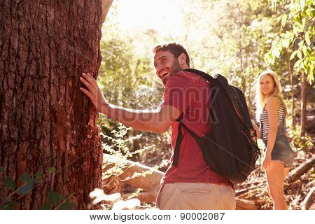 Couple Pausing By Tree Trunk In On Walk Through Forest
