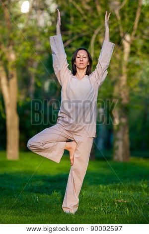 Practicing yoga in the morning, with trees  background