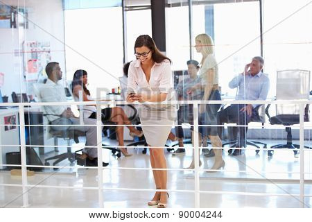 Woman using phone during office meeting