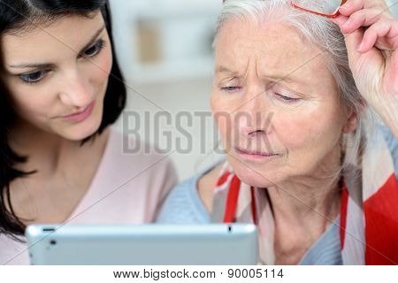 Helping old woman use a tablet computer